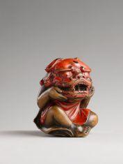 Netsuke, enfant enlevant un masque de Shishi Bois laqué rouge Japon, époque Edo